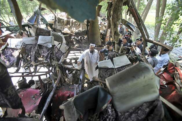 Pakistani police officers check the wreckage of a bus that exploded when a bomb planted in it went off on the outskirts of Peshawar, Pakistan, Friday, June 8, 2012. A bomb tore through a bus carrying government employees and other civilians in northwestern Pakistan on Friday, killing several people in an attack that served as a reminder of the continued militant threat despite a significant drop in violence over the past year, officials said. (AP Photo/Mohammad Sajjad) Photo: Mohammad Sajjad, Associated Press