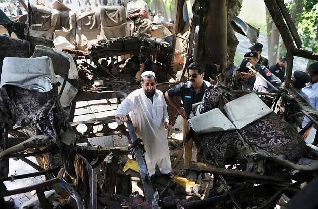 Pakistani security officials examine the wreckage of a destroyed bus after a bomb explosion on the outskirts of Peshawar on June 8, 2012. A bomb blast ripped through a Pakistani bus on June 8, killing at least 18 people, including six women and a child, on the outskirts of Pakistan's northwestern city of Peshawar, police said. More than 40 other people were wounded in the attack on a bus rented by the government to take staff home after work in the northwestern province of Khyber Pakhtunkhwa. AFP PHOTO / A. MAJEEDA. MAJEED/AFP/GettyImages Photo: A. Majeed, AFP/Getty Images