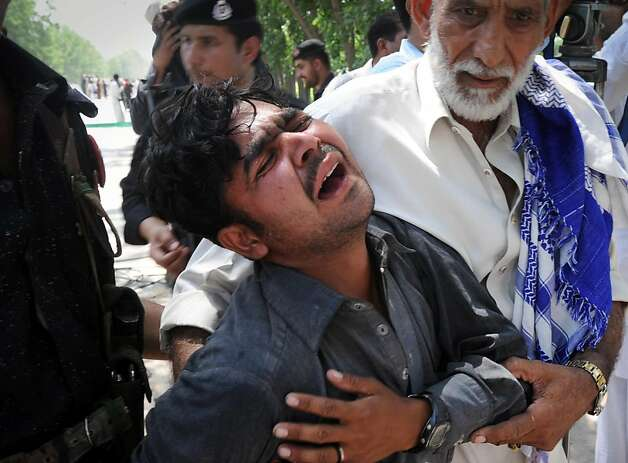 Pakistani men comfort a mourner after the killing of his relatives in a bomb explosion on the outskirts of Peshawar on June 8, 2012. A bomb blast ripped through a Pakistani bus on June 8, killing at least 18 people, including six women and a child, on the outskirts of Pakistan's northwestern city of Peshawar, police said. More than 40 other people were wounded in the attack on a bus rented by the government to take staff home after work in the northwestern province of Khyber Pakhtunkhwa. AFP PHOTO / A. MAJEEDA. MAJEED/AFP/GettyImages Photo: A. Majeed, AFP/Getty Images
