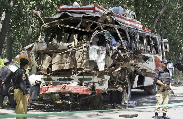 Pakistani policemen stand by the wreckage of a bus that exploded when a bomb planted in it went off on the outskirts of Peshawar, Pakistan, Friday, June 8, 2012. A bomb tore through a bus carrying government employees and other civilians in northwestern Pakistan killing several people in an attack that served as a reminder of the continued militant threat despite a significant drop in violence over the past year, officials said. (AP Photo/Mohammad Sajjad) Photo: Mohammad Sajjad, Associated Press