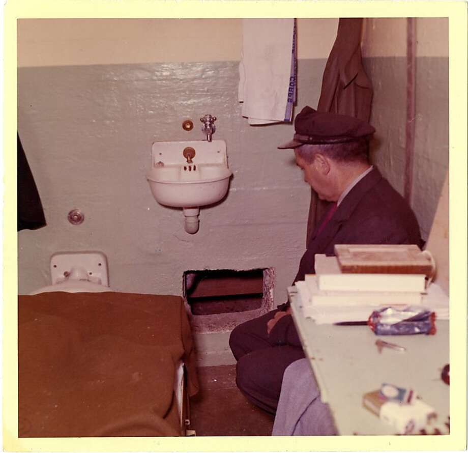 This 1962 photo from the U.S. Penitentiary Alcatraz shows Frank Morris's cell and Senior Officer Howard Waldron looking at the point of escape. Photo: Handout Photo, U. S. Penitentiary Alcatraz