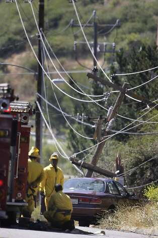 A vehicle that knocked down a power pole and caused a brush fire is seen on Mountain Boulevard as emergency responders stand near it on Friday, June 8, 2012 in Oakland, Calif. Photo: Lea Suzuki, The Chronicle