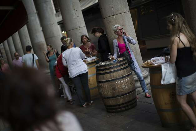 People are seen in a bar near to a food market in Barcelona, Spain, Saturday June 9 2012. Spain will ask for a bank bailout from the eurozone, becoming the fourth and largest country to seek help since the single currency bloc's debt crisis erupted. (AP Photo/Emilio Morenatti) Photo: Emilio Morenatti, Associated Press