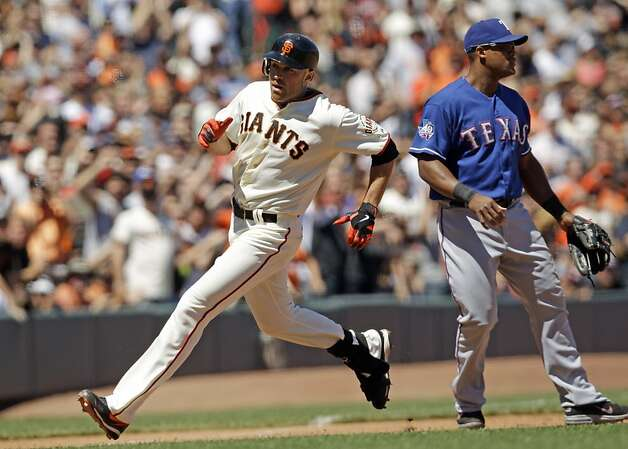 San Francisco Giants' Nate Schierholtz, left, arrives safely at third base next to Texas Rangers third baseman Adrian Beltre, right, on an RBI triple during the sixth inning of a baseball game in San Francisco, Saturday, June 9, 2012. The Giants won 5-2. (AP Photo/Marcio Jose Sanchez) Photo: Marcio Jose Sanchez, Associated Press
