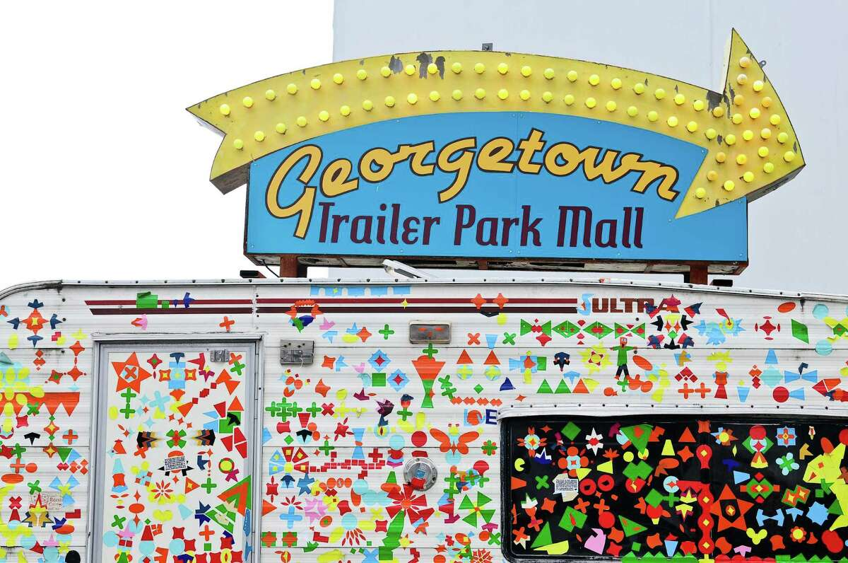 A trailer covered in stickers points the way to the year-round trailer park mall.