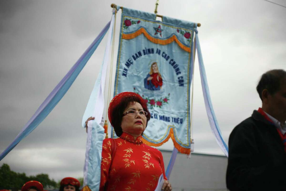A woman walks in a parade around the Vietnamese Martyrs Parish in Seattle during an Eucharistic Adoration ceremony on Saturday, June 9, 2012.