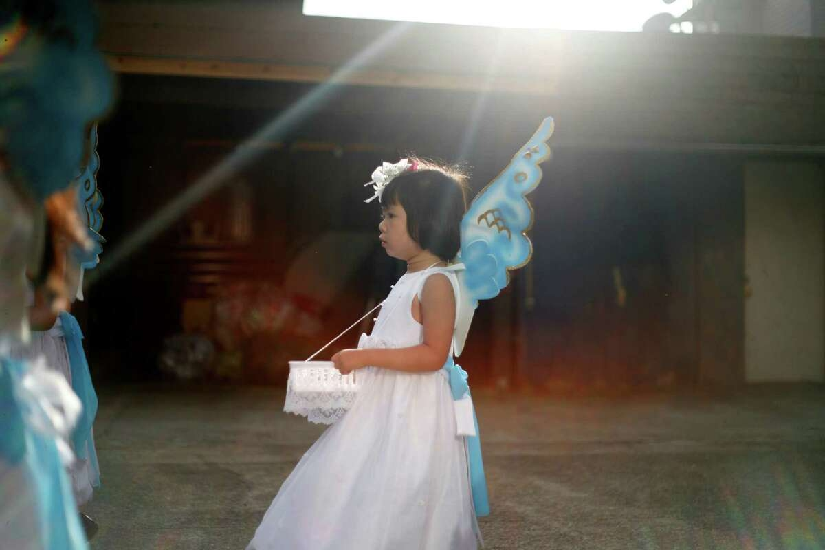 Elena Dao, 3, dresses as an angel.