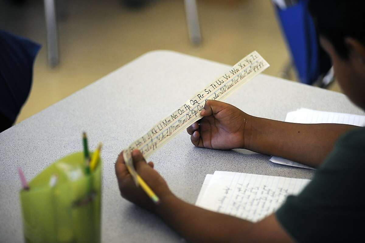 A student looks at a cursive letter guide while working on a writing assignment in Oceanhawk's 3rd grade class at Encompass Academy in East Oakland, CA June 6th, 2012