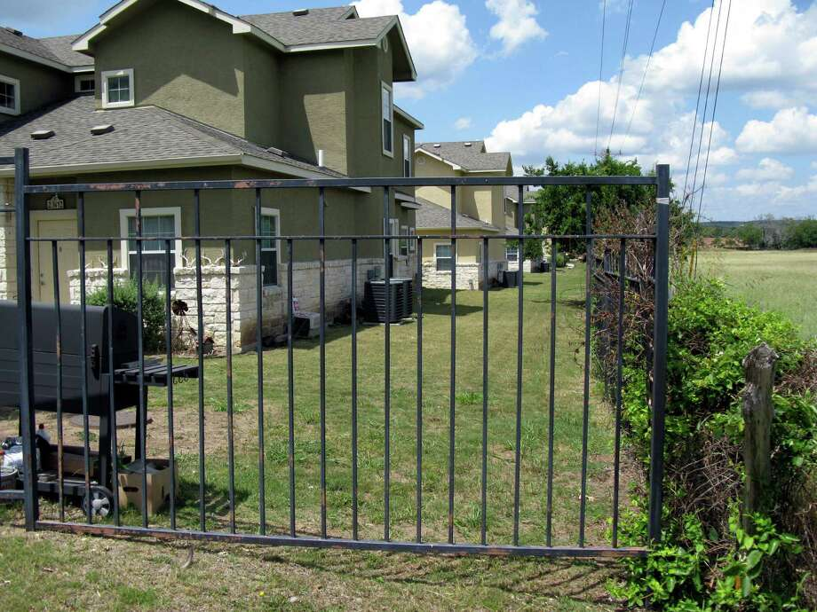 A metal fence blocks the access easement that runs along the side of the Stone Creek Village Apartments in Boerne. Photo: Zeke MacCormack, San Antonio Express-News / San Antonio Express-News