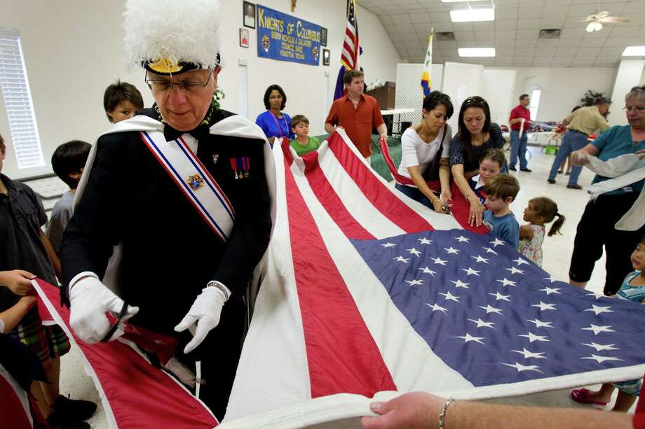 Merv Albert, top left, cuts apart a worn flag during a flag retirement ceremony at the Bishop Nicholas A. Gallagher Council 8482 Knights of Columbus Hall Sunday, June 10, 2012, in Houston. The Knights, helped by youths from the Boy Scouts, Girl Scouts and American Heritage Girls, retired several dozen worn American flags in a ceremony at the Knights' hall. Photo: Brett Coomer, Houston Chronicle / © 2012 Houston Chronicle