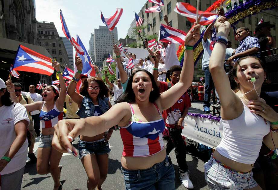 People march in the National Puerto Rican Day Parade on New York's Fifth Avenue, Sunday, June 10, 2012. The parade has been an annual event in New York since 1958 and has grown to be one of the city's largest. (AP Photo/Richard Drew) Photo: Richard Drew, Associated Press / AP