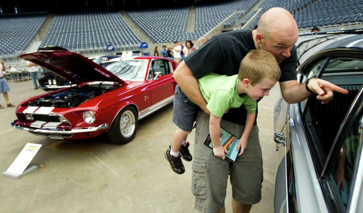 Byron Moore, 5, gets a lift from his dad, Andrew Moore, to take a look at the interior of a 1968 Oldsmobile during the 9th Annual Classy Chassis Concours d' Elegance car show at Reliant Stadium Sunday, June 10, 2012, in Houston. The show featured more than 100 unique and rare automobiles, with proceeds benefitting Shriners Hospitals for Children.