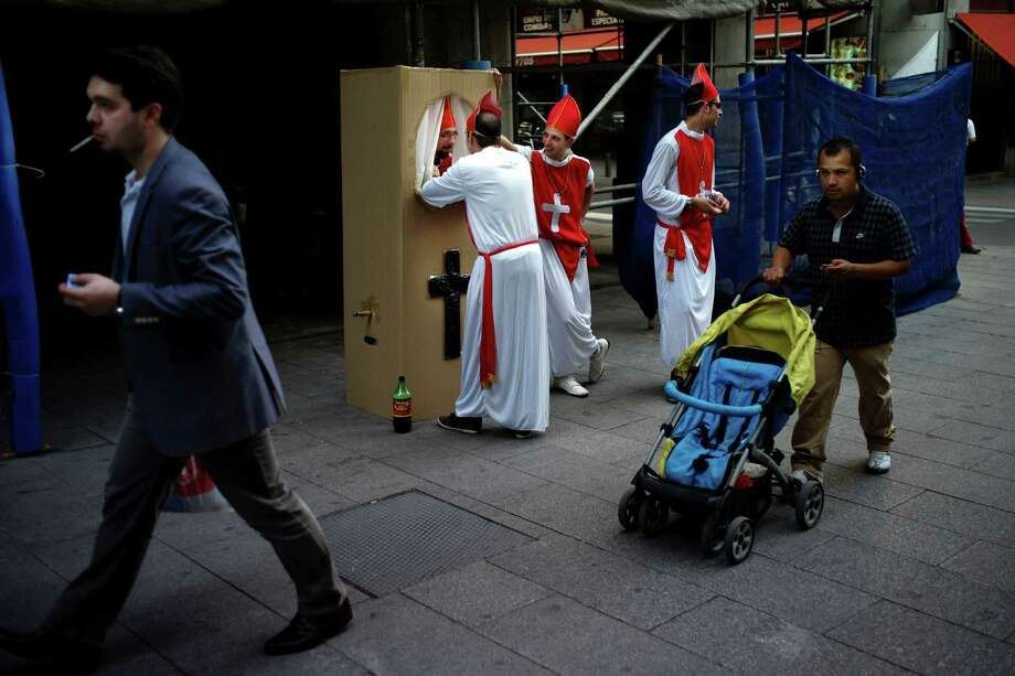 Spaniards dressed up like Bishops for a stag party play the role of a confessor in downtown Madrid, Saturday June 9 2012. Spain will ask for a bank bailout from the eurozone, becoming the fourth and largest country to seek help since the single currency bloc's debt crisis erupted.(AP Photo/Daniel Ochoa de Olza) Photo: Daniel Ochoa De Olza / AP