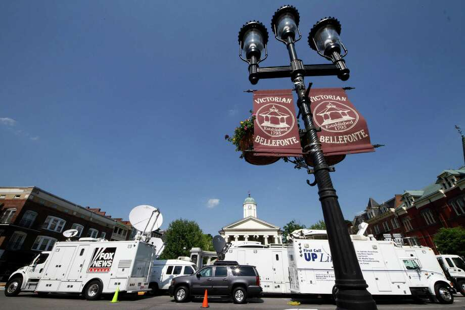 Television satellite trucks line South Allegheny Street in front of the Centre County Courthouse in Bellefonte, Pa.,  Sunday, June 10, 2012 in preparation for opening statements in the child sexual abuse trial of former Penn State Football assistant football coach Jerry Sandusky on Monday morning. (AP Photo/Gene J. Puskar) Photo: Gene J. Puskar / AP