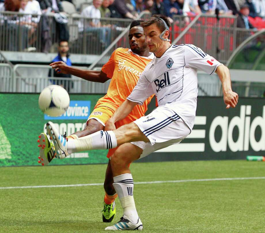 VANCOUVER, CANADA - JUNE 10:  Alain Rochat #4 of the Vancouver Whitecaps FC and Warren Creavallez #5 of the Houston Dynamo compete for the ball during their MLS game June 10, 2012 in Vancouver, British Columbia, Canada. Photo: Jeff Vinnick, Getty Images / 2012 Getty Images