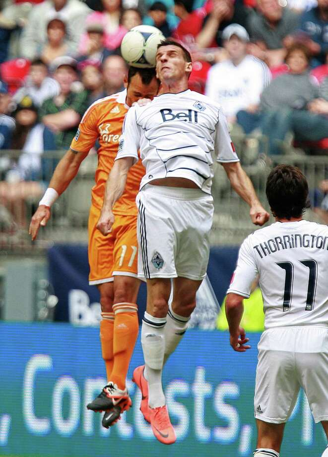 VANCOUVER, CANADA - JUNE 10:  Sebastien Le Toux #7 of the Vancouver Whitecaps FC and Brad Davis #11 of the Houston Dynamo take to the air for the ball during their MLS game June 10, 2012 in Vancouver, British Columbia, Canada. Photo: Jeff Vinnick, Getty Images / 2012 Getty Images