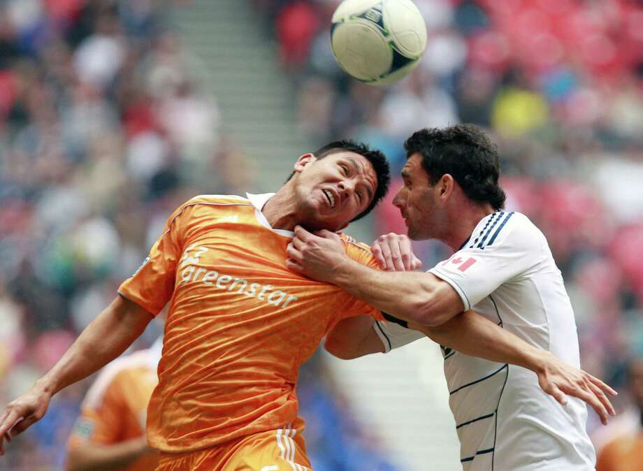 VANCOUVER, CANADA - JUNE 10:  Brian Ching #25 of the Houston Dynamo and Martin Bonjour #15 of the Vancouver Whitecaps FC compete for the ball during their MLS game June 10, 2012 in Vancouver, British Columbia, Canada. Photo: Jeff Vinnick, Getty Images / 2012 Getty Images