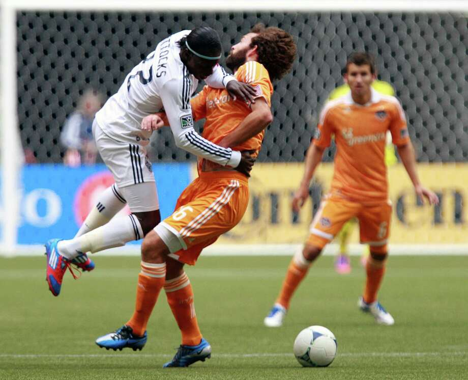 VANCOUVER, CANADA - JUNE 10:  Darren Mattocks #22 of the Vancouver Whitecaps FC and Adam Moffat #16 of the Houston Dynamo collide during their MLS game June 10, 2012 in Vancouver, British Columbia, Canada. Photo: Jeff Vinnick, Getty Images / 2012 Getty Images