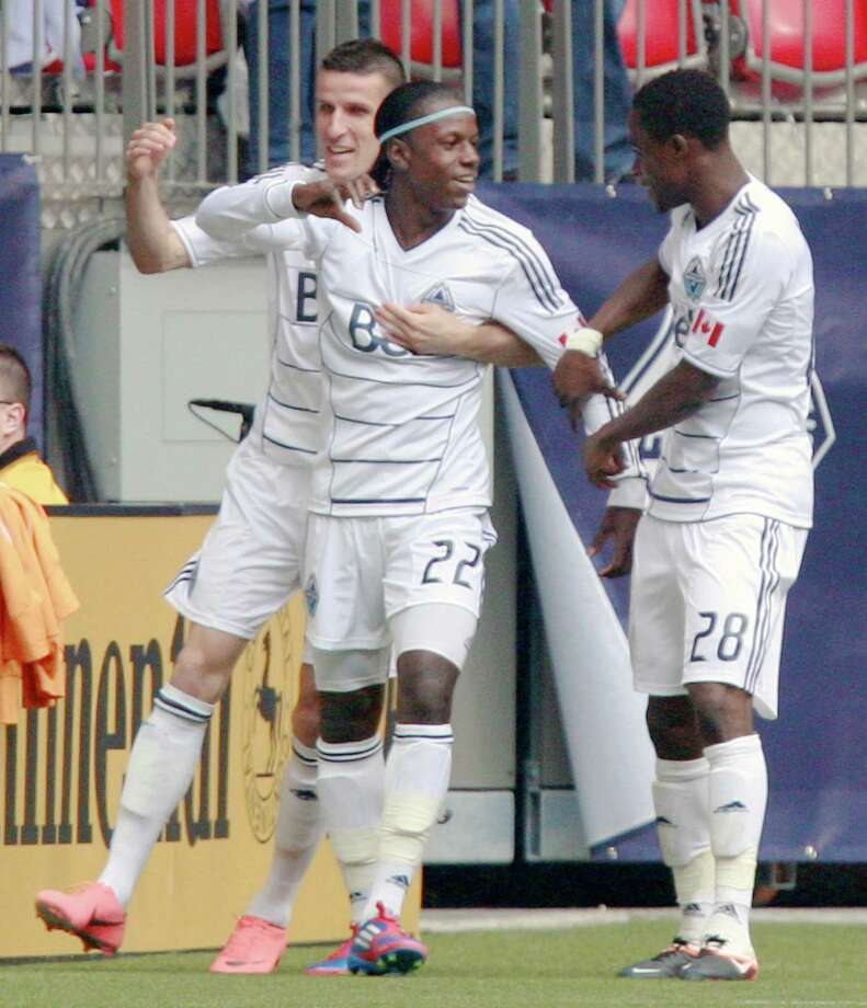 VANCOUVER, CANADA - JUNE 10:  Sebastien Le Toux #7 and Gershon Koffie #28 celebrate with goal scorer Darren Mattocks #22 of the Vancouver Whitecaps FC against the Houston Dynamo during their MLS game June 10, 2012 in Vancouver, British Columbia, Canada. Photo: Jeff Vinnick, Getty Images / 2012 Getty Images