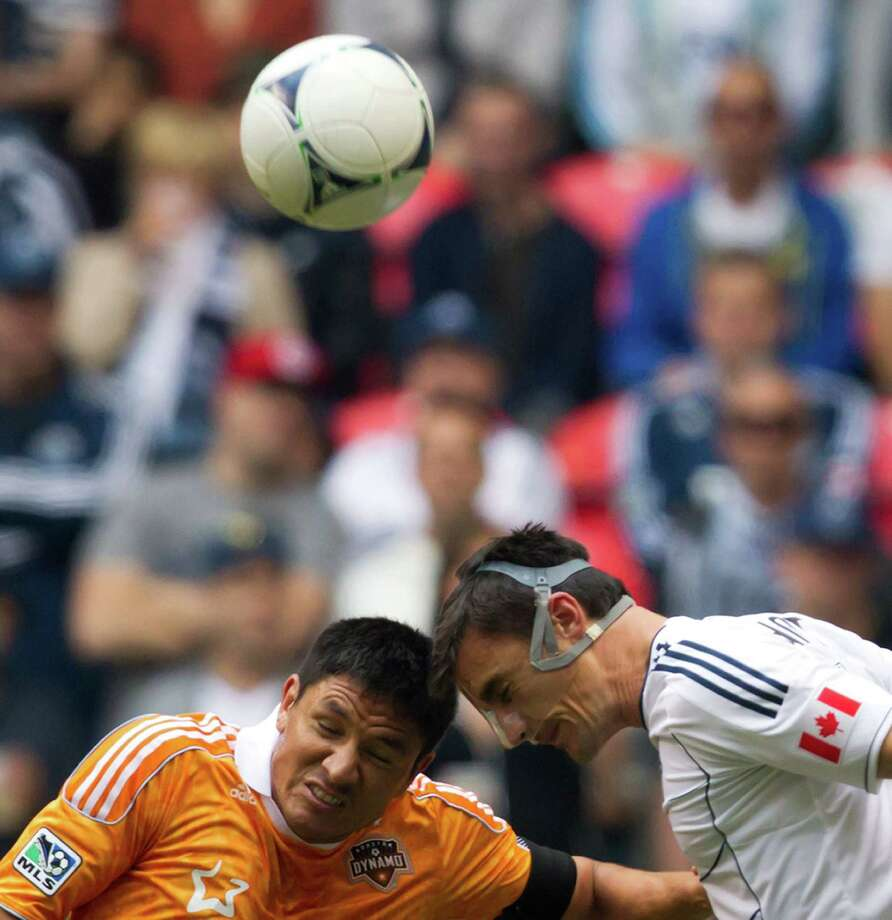 Houston Dynamo's Brian Ching, left, and Vancouver Whitecaps' Alain Rochat, of Switzerland, vie for the ball during the first half of an MLS soccer game in Vancouver, British Columbia, on Sunday, June 10, 2012. (AP Photo/The Canadian Press, Darryl Dyck) Photo: Darryl Dyck, Associated Press / The Canadian Press