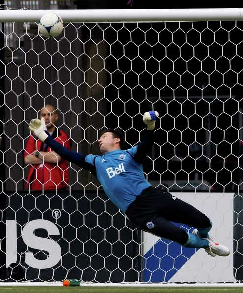 Vancouver Whitecaps goalkeeper Joe Cannon gets his hand on a Houston Dynamo shot to make the save du