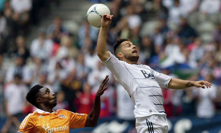Houston Dynamo's Warren Creavalle, left, watches as Vancouver Whitecaps' Davide Chiumiento, of Switzerland, misses the ball during the first half of an MLS soccer game in Vancouver, British Columbia, on Sunday, June 10, 2012. (AP Photo/The Canadian Press, Darryl Dyck) Photo: Darryl Dyck, Associated Press / The Canadian Press
