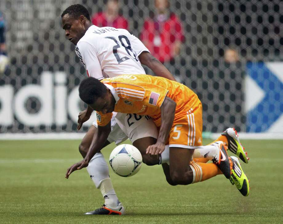 Vancouver Whitecaps' Gershon Koffie, top, of Ghana, and Houston Dynamo's Warren Creavalle collide during the first half of an MLS soccer game in Vancouver, British Columbia, on Sunday, June 10, 2012. (AP Photo/The Canadian Press, Darryl Dyck) Photo: Darryl Dyck, Associated Press / The Canadian Press