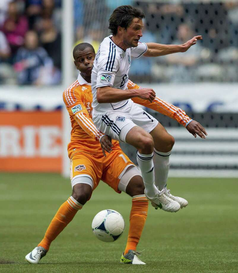 Vancouver Whitecaps' John Thorrington, right, jumps to avoid the tackle by Houston Dynamo's Luiz Camargo, of Brazil, during the first half of an MLS soccer game in Vancouver, British Columbia, on Sunday, June 10, 2012. (AP Photo/The Canadian Press, Darryl Dyck) Photo: Darryl Dyck, Associated Press / The Canadian Press