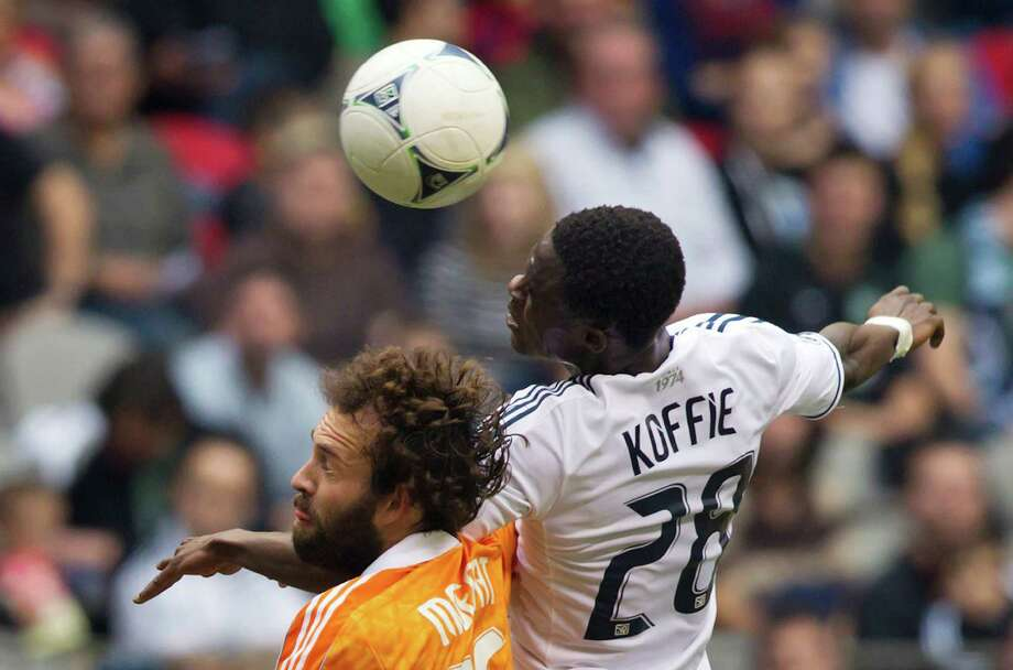 Houston Dynamo's Adam Moffat, left, of Scotland, and Vancouver Whitecaps' Gershon Koffie, of Ghana, jump for the ball during the first half of an MLS soccer game in Vancouver, British Columbia, on Sunday, June 10, 2012. (AP Photo/The Canadian Press, Darryl Dyck) Photo: Darryl Dyck, Associated Press / The Canadian Press