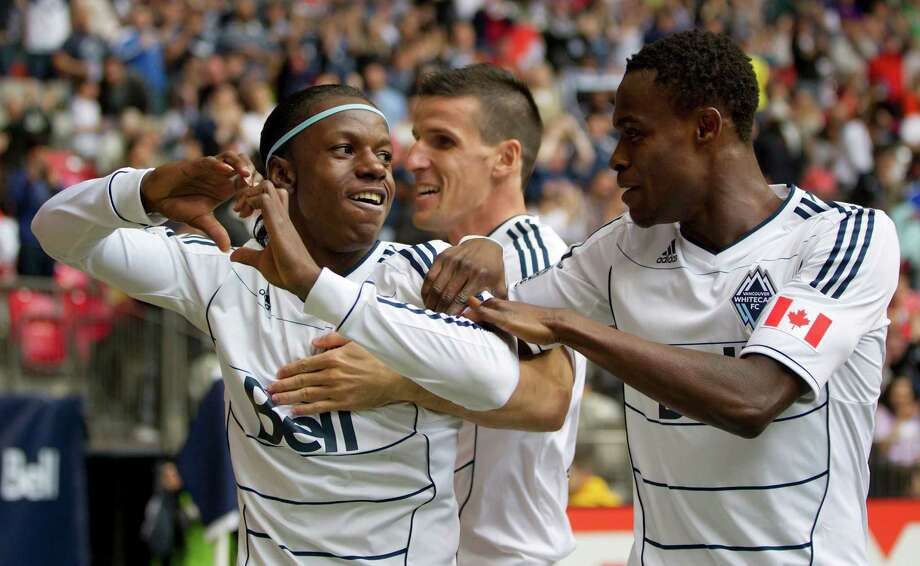 Vancouver Whitecaps' Darren Mattocks, of Jamaica, Sebastien Le Toux, of France, and Gershon Koffie, of Ghana, from left, celebrate Mattocks' goal against the Houston Dynamo during the first half of an MLS soccer game in Vancouver, British Columbia, on Sunday, June 10, 2012. (AP Photo/The Canadian Press, Darryl Dyck) Photo: Darryl Dyck, Associated Press / The Canadian Press