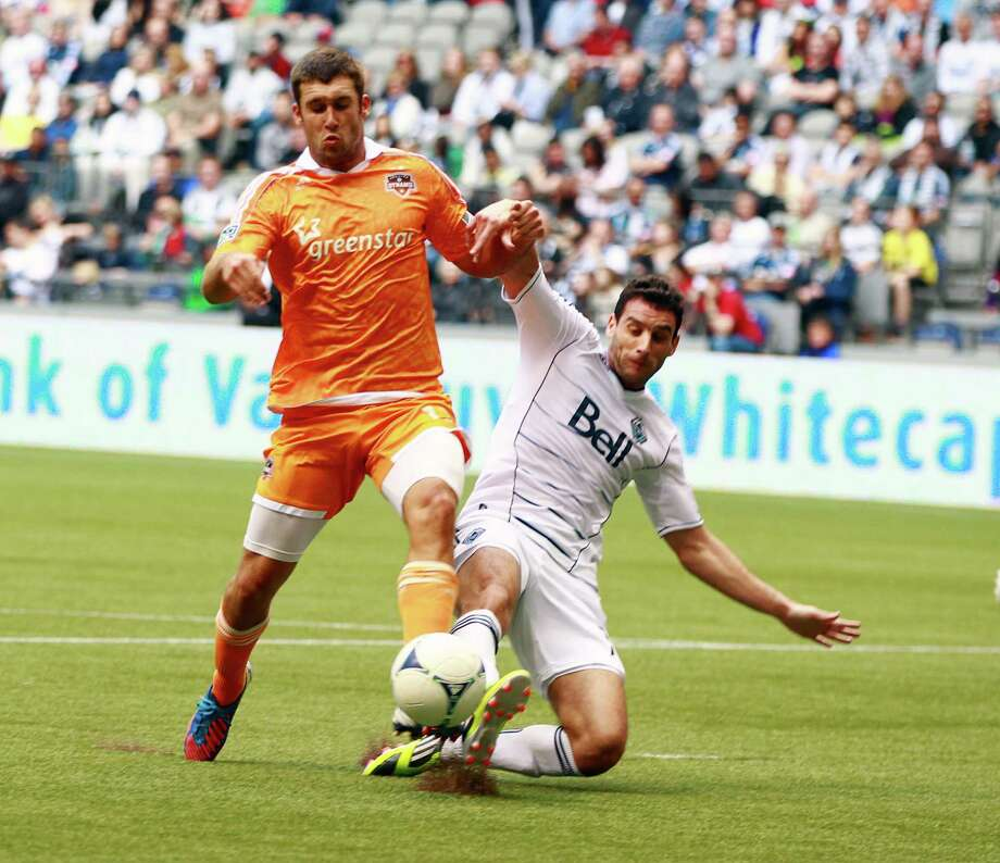 VANCOUVER, CANADA - JUNE 10:  Will Bruin #12 of the Houston Dynamo and Martin Bonjour #15 of the Vancouver Whitecaps FC are locked in battle during their MLS game June 10, 2012 in Vancouver, British Columbia, Canada. Photo: Jeff Vinnick, Getty Images / 2012 Getty Images