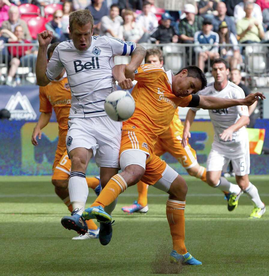 Vancouver Whitecaps' Jay DeMerit, left, and Houston Dynamo's Brian Ching vie for the ball during the second half of an MLS soccer game in Vancouver, British Columbia, on Sunday, June 10, 2012. (AP Photo/The Canadian Press, Darryl Dyck) Photo: Darryl Dyck, Associated Press / The Canadian Press