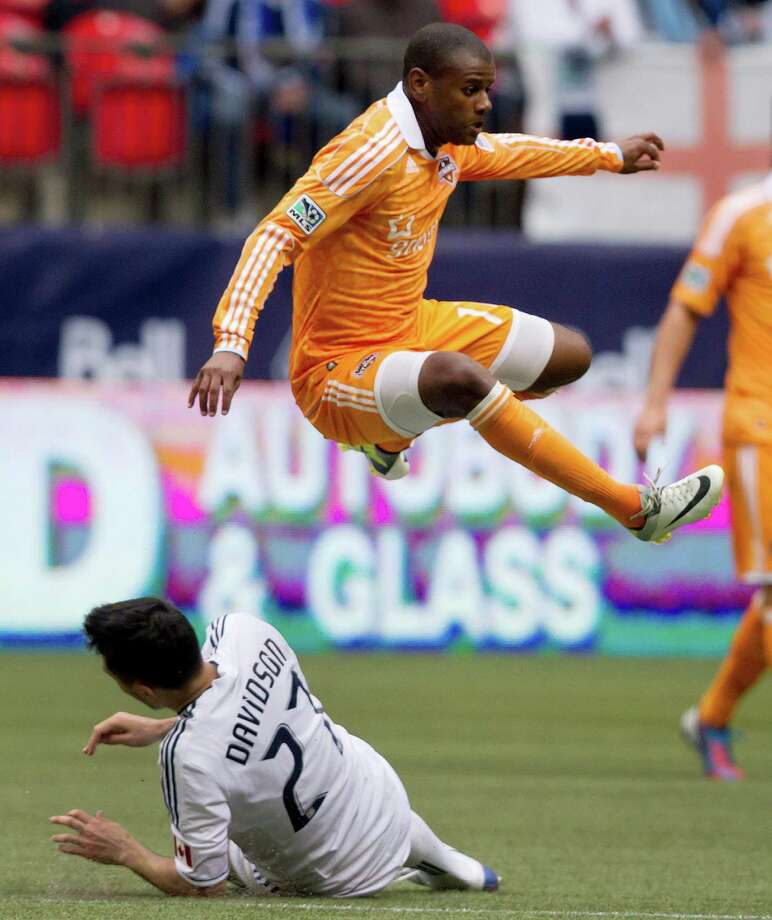 Houston Dynamo's Luiz Camargo, right, of Brazil, leaps over Vancouver Whitecaps' Jun Marques Davidson, of Japan, during the second half of an MLS soccer game in Vancouver, British Columbia, on Sunday, June 10, 2012. (AP Photo/The Canadian Press, Darryl Dyck) Photo: Darryl Dyck, Associated Press / The Canadian Press