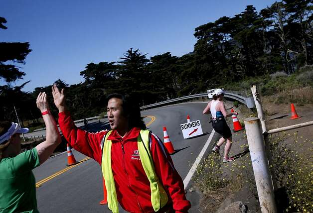 Tenzin Yougyal, of Richmond, offers much-welcomed high-fives to runners competing in the Escape from Alcatraz Triathlon in San Francisco, Calif., Sunday, June 10, 2012. Photo: Sarah Rice, Special To The Chronicle