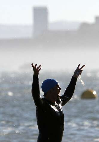 A swimmer celebrates completing the first leg of the Escape from Alcatraz Triathlon in San Francisco, Calif., Sunday, June 10, 2012.  After swimming from Alcatraz, athletes bike 18 miles then run 8 miles. Photo: Sarah Rice, Special To The Chronicle