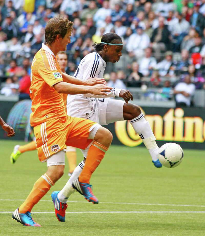 VANCOUVER, CANADA - JUNE 10:  Darren Mattocks #22 of the Vancouver Whitecaps FC, who scored twice, pulls away from Bobby Boswell #32 of the Houston Dynamo during their MLS game June 10, 2012 in Vancouver, British Columbia, Canada. Photo: Jeff Vinnick, Getty Images / 2012 Getty Images