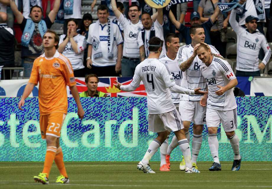 Houston Dynamo's Brian Ownby, left, walks away as Vancouver Whitecaps' Alain Rochat, of Switzerland; Sebastien Le Toux, of France; Eric Hassli, of France; and Jordan Harvey, left to right, celebrate Harvey's goal during the first half of an MLS soccer game in Vancouver, British Columbia, on Sunday, June 10, 2012. (AP Photo/The Canadian Press, Darryl Dyck) Photo: DARRYL DYCK, Associated Press / The Canadian Press