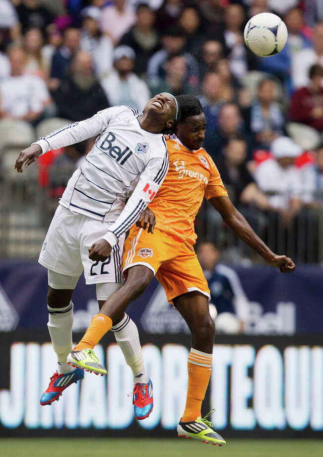 Vancouver Whitecaps' Darren Mattocks, left, of Jamaica, heads the ball away from Houston Dynamo's Warren Creavalle during the second half of an MLS soccer game in Vancouver, British Columbia, on Sunday, June 10, 2012. (AP Photo/The Canadian Press, Darryl Dyck) Photo: Darryl Dyck, Associated Press / The Canadian Press