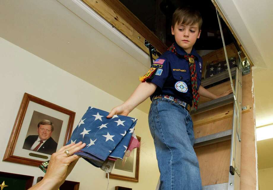 Mark Morrison, 9, hands down a worn flag from the attic of the Bishop Nicholas A. Gallagher Council 8482 Knights of Columbus Hall before a flag retirement ceremony Sunday, June 10, 2012, in Houston. The Knights, helped by youths from the Boy Scouts, Girl Scouts and American Heritage Girls, retired several dozen worn American flags in a ceremony at the Knights' hall. ( Brett Coomer / Houston Chronicle ) Photo: Brett Coomer / © 2012 Houston Chronicle