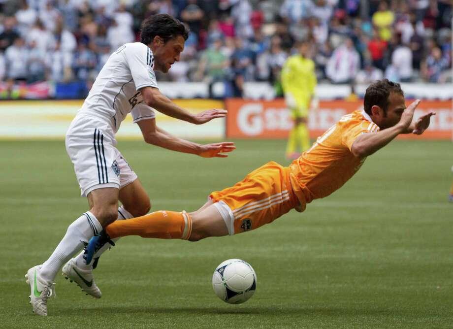 The Whitecaps' John Thorrington, left, knocks the Dynamo's Brad Davis off the ball. Photo: Darryl Dyck / The Canadian Press
