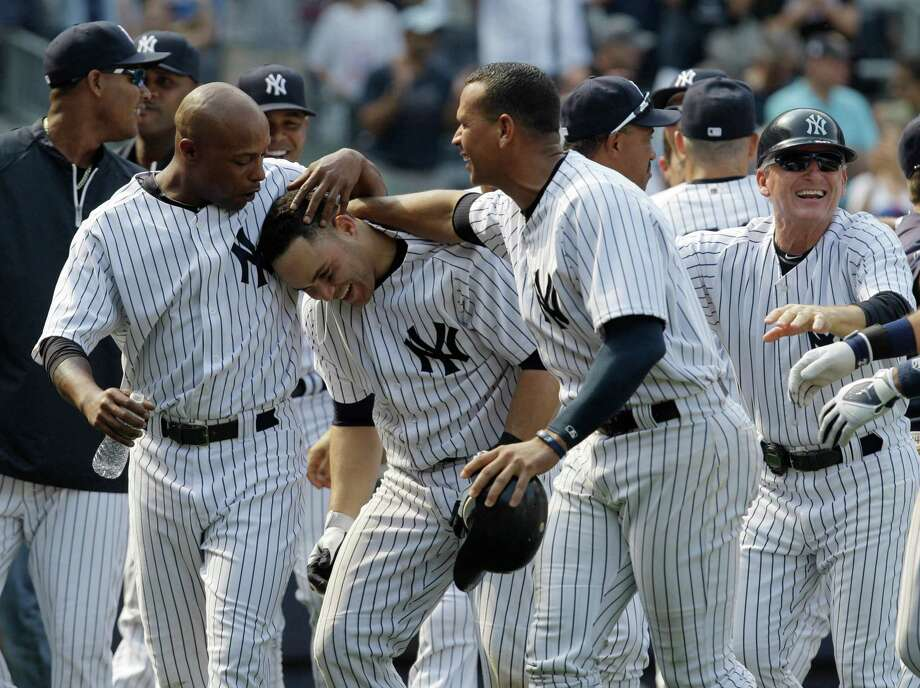 New York Yankees Dewayne Wise, left, and Alex Rodriguez, right, celebrate with  Russell Martin, who hit a walk-off solo home run to beat the Mets 5-4. Photo: Kathy Willens / AP