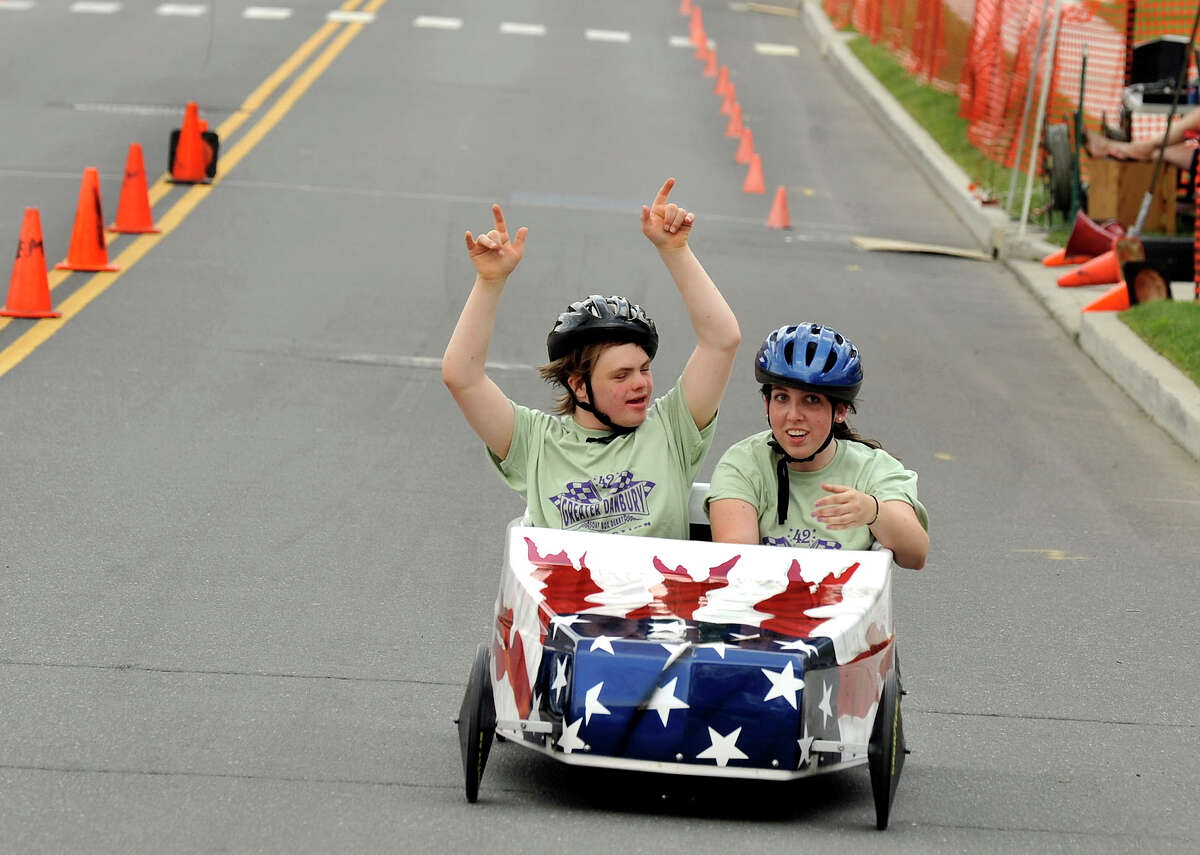 Jack Johnson, 16, of Danbury, and Megan Strand, 20, of New Milford, cross the finish line to win their race in the Danbury Soap Box Derby Sunday, June 10, 2012.