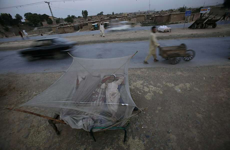 Two Pakistani men sleep on a bed covered with a mosquito net, on a roadside on the outskirts of Islamabad, Pakistan, early Monday, June 11, 2012. Many Pakistanis sleep outdoors to escape the heat trapped in their homes during the summer months. (AP Photo/Muhammed Muheisen) Photo: Muhammed Muheisen, Associated Press