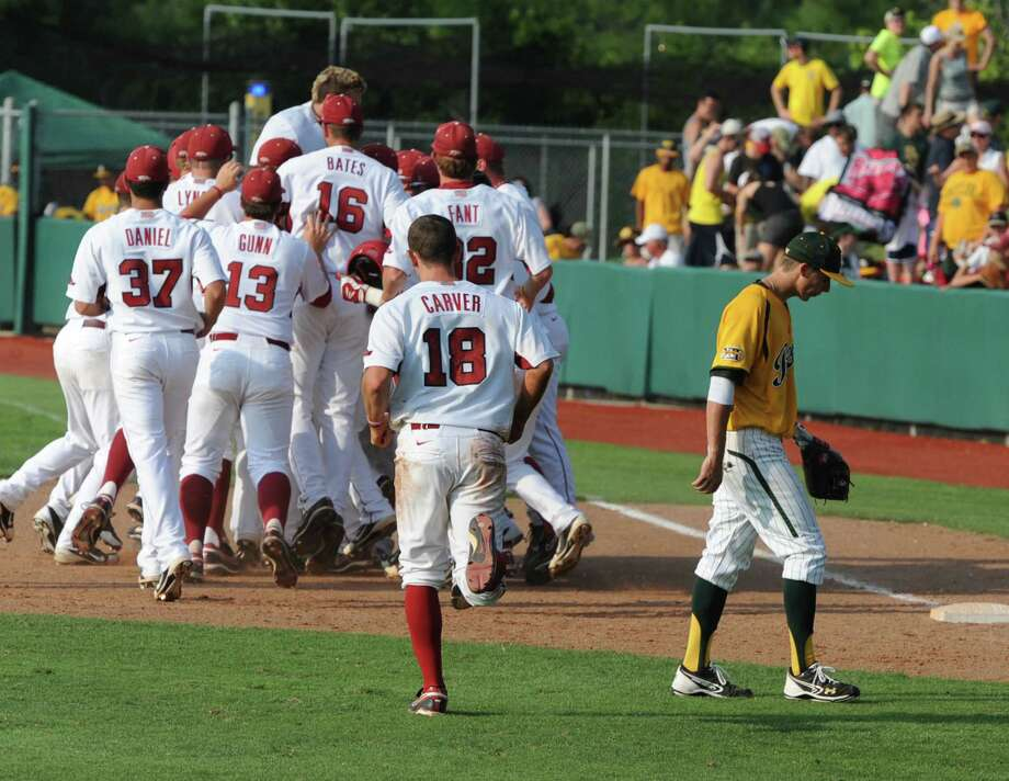 Baylor's Lawton Langford, right, leaves the field as Arkansas players celebrate after scoring the winning run in the bottom of the ninth inning of an NCAA college baseball tournament super regional game on Sunday, June 10, 2012, in Waco. Photo: AP Photo/Waco Tribune Herald, Rod Aydelotte