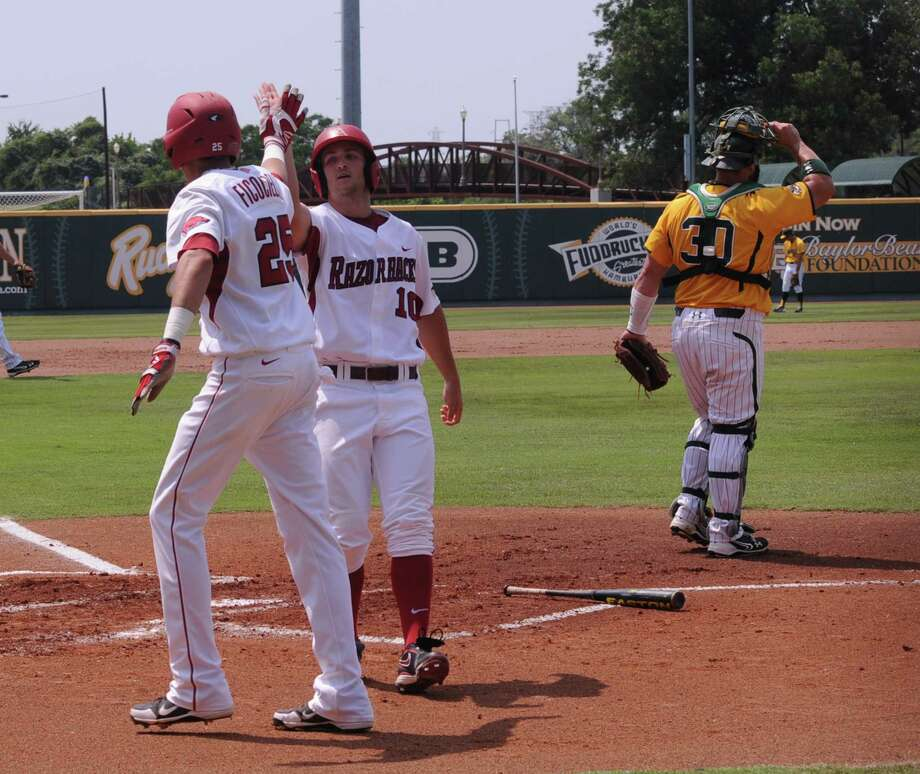 Arkansas' Joe Serrano (10), center high-fives teammate Dominic Ficociello (25) after scoring in the first  inning of an NCAA college baseball tournament super regional game on Sunday, June 10, 2012, in Waco. Baylor catcher Josh Ludy (30) looks on. Photo: AP Photo/Waco Tribune Herald, Rod Aydelotte