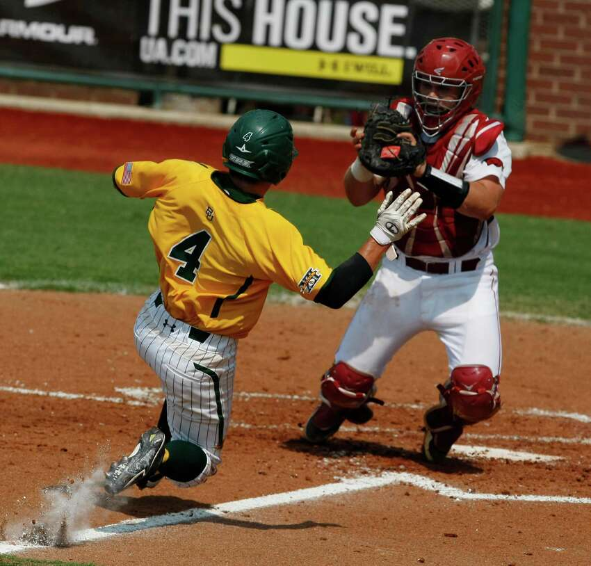 Arkansas catcher John Clay Reeves, right, tags out Baylor's Nathan Orf (4) in the third inning of an NCAA college baseball tournament super regional game on Sunday, June 10, 2012, in Waco.