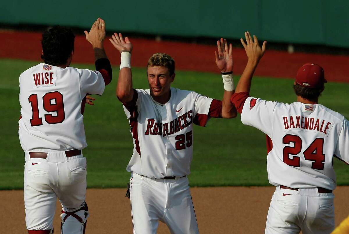 Arkansas players Dominic Ficociello (25), Jake Wise (19) and DJ Baxendale (24) celebrate after defeating Baylor folloiwng their NCAA college baseball tournament super regional game on Sunday, June 10, 2012, in Waco.