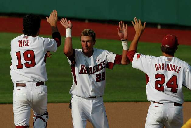 Arkansas players Dominic Ficociello (25), Jake Wise (19) and DJ Baxendale (24) celebrate after defeating Baylor folloiwng their NCAA college baseball tournament super regional game on Sunday, June 10, 2012, in Waco. Photo: AP Photo/Waco Tribune Herald, Jose Yau