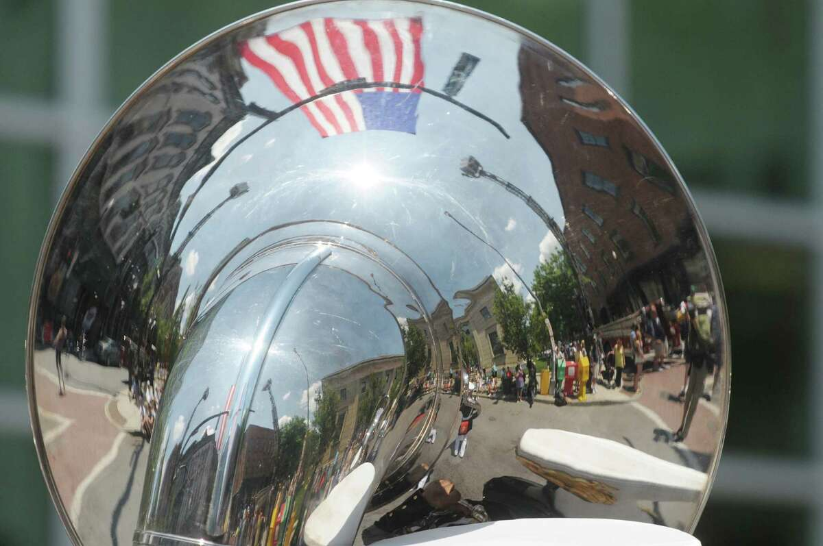 A reflection in the tuba of a United States Marine Corps Band members as they march in the Troy Flag Day Parade on Sunday, June 10, 2012 in Troy, NY. (Paul Buckowski / Times Union)