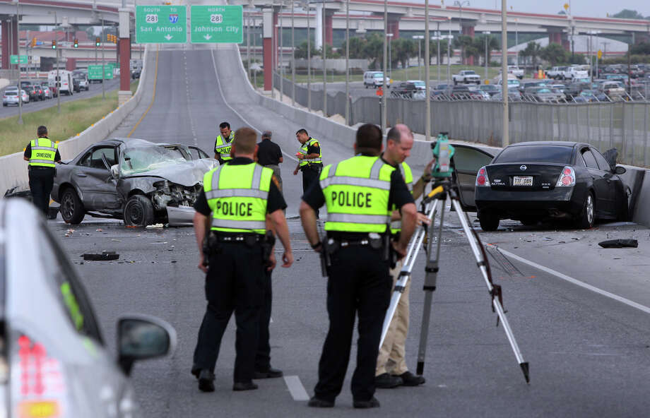 San Antonio police investigate the scene of a fatal accident that took place Monday June 11, 2012 shortly after 7:00 a.m. on a westbound portion of Loop 410 between Wetmore road and Airport Boulevard. Photo: John Davenport/San Antonio Express-News
